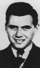 <p>Alman doktor ve SS yüzbaşı Josef Mengele. 1943'te Auschwitz SS garnizon doktoru (Standortartz) unvanını aldı. Mevkisi gereği çalışabilecek denli formda olanları ve gaz odasına gitmeye mahkumları seçmek ve ayırmaktan sorumluydu. Mengele ayrıca kampta kalanlar, özellikle de ikizler üzerinde insan deneyleri yürüttü. Yer ve tarih bilinmiyor.</p>