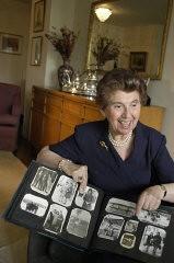 "<p><a href=""/narrative/10466"">Regina Gelb</a> displays an album of her prewar family photographs. 2004.</p>"