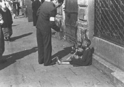 "<p>A Warsaw ghetto resident gives money to two <a href=""/narrative/2562"">children</a> on a <a href=""/narrative/2014"">Warsaw</a> ghetto street. Warsaw, Poland, between October 1940 and April 1943.</p>"