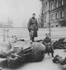 <p>A German soldier stands on a toppled Polish monument. Krakow, Poland, 1940.</p>