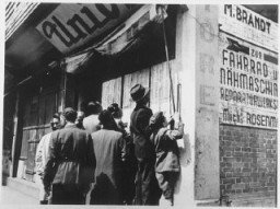 "<p>Jewish refugees in <a href=""/narrative/9660/en"">Shanghai</a> look for names of relatives and friends who may have survived the war. Awaiting repatriation, these displaced persons were under <a href=""/narrative/7232/en"">United Nations Relief and Rehabilitation Administration care</a>. China, 1946.</p>"