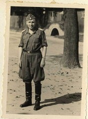 """<p>Photograph of Karl Höcker. He is standing in front of an air raid shelter.</p> <p><span style=""""font-weight: 400;"""">From <a href=""""/narrative/10876/en"""">Karl Höcker's photograph album</a>, which includes both documentation of official visits and ceremonies at Auschwitz as well as more personal photographs depicting the many social activities that he and other members of the Auschwitz camp staff enjoyed. These rare images show Nazis singing, hunting, and even trimming a Christmas tree. They provide a chilling contrast to the photographs of thousands of Hungarian Jews deported to Auschwitz at the same time. </span></p>"""