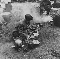 "<p>Soon after liberation, camp survivors cook in a field. <a href=""/narrative/8176"">Bergen-Belsen</a>, Germany, after April 15, 1945.</p>