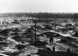 <p>View of a camp for Soviet prisoners of war, showing the holes dug into the ground that served as shelter. The camp was located south of Hamburg in northern Germany. Wietzendorf, Germany, 1941–42.</p>