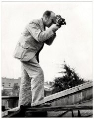 """<p><a href=""""/narrative/11384"""">Julien Bryan</a> was an important US documentary filmmaker and photographer who captured the everyday life, work, and culture of individuals and communities in many countries around the globe.</p> <p>Bryan was filming in western Europe in the summer of 1939. In the first week of September 1939, Bryan made his way to Warsaw just as all foreign reporters, diplomats, and Polish government officials were fleeing the capital in the wake of the German invasion. One of the few foreign photographers left in the city, he risked his life to record besieged Warsaw. This image shows him filming during the <a href=""""/narrative/2103"""">German invasion of Warsaw in 1939</a>.</p>"""
