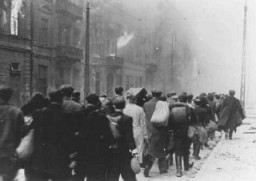 "<p>Deportation of Jews from the Warsaw ghetto during the <a href=""/narrative/3636/en"">ghetto uprising</a>. The original German caption reads: ""To the Umschlagplatz."" Warsaw, Poland, May 1943.</p>"