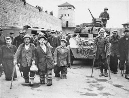 "<p>Soviet and Polish prisoners with disabilities stand in front of a tank of the <a href=""/narrative/7842"">11th Armored Division</a>, US Third Army. This photograph was taken at the <a href=""/narrative/3880"">Mauthausen</a> concentration camp immediately after <a href=""/narrative/2317"">liberation</a>. Austria, May 5–7, 1945.</p>"