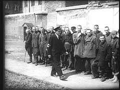 """<p>Depois que os alemães criaram o gueto de Varsóvia, em 1940, o [antigo] Conselho Judaico da cidade tornou-se responsável por prover todos os tipos de serviços municipais naquela área. Neste documentário alemão, vêem-se os encarcerados da """"Prisão Judaica"""" [situada  dentro do gueto] correndo para o pátio e andando em círculos para serem inspeccionados.</p>"""