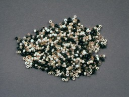 "<p>These tiny black, white, gold, and clear glass beads used by Rachel ""Chelly"" de Groot from November 1942 to April 1944 and recovered by her brother Louis after the war. Chelly used the beads to make handicrafts.</p>