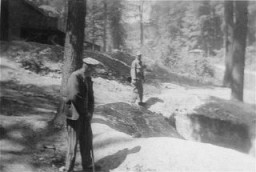 Двое уцелевших узников возле одной из ям с пеплом людей, сожженных в концлагере Дора-Миттельбау, расположенном близ Нордхаузена.