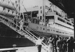"<p>Jewish refugees from Nazi Germany, passengers on the <a href=""/narrative/4719/en""><em>St. Louis</em></a>, disembark in the port of Antwerp. Cuba and the United States denied entry to these refugees. Belgian police guard the gangway. Antwerp, Belgium, June 17, 1939.</p>"