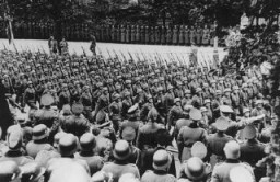 "<p>Adolf Hitler (lower right) gives Nazi salute as he reviews victorious German troops. <a href=""/narrative/2014/en"">Warsaw</a>, Poland, October 5, 1939.</p>"