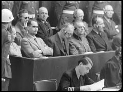 <p>Defendant Hermann Göring, seated at left in the dock, listens as US Chief Prosecutor Robert Jackson interrogates witness Albert Kesselring about the Luftwaffe (German Air Force).</p>