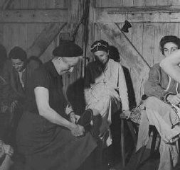 "<p>Soon after <a href=""/narrative/2317/en"">liberation</a>, a British woman helps a camp survivor try on shoes. Bergen-Belsen, Germany, after May 1945.</p>"
