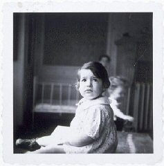 "<p>A young girl in a home for Jewish infants waiting for their <a href=""/narrative/7747/en"">families</a> to claim them or be adopted. Etterbeek, Belgium, after 1945.</p>"