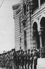 """<p>A flag bearing a swastika is raised over the city hall in Sarajevo after German forces captured the city. Sarajevo, <a href=""""/narrative/6153"""">Yugoslavia</a>, April 16, 1941.</p>"""