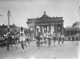 "<p>On August 1, 1936, Hitler opened the 11th Summer <a href=""/narrative/7139"">Olympic Games</a>. Inaugurating a new Olympic ritual, a lone runner arrived bearing a <a href=""/narrative/10944"">torch</a> carried by relay from the site of the ancient Games in Olympia, Greece. This photograph shows an Olympic torch bearer running through Berlin, passing by the Brandenburg Gate, shortly before the opening ceremony. Berlin, Germany, July-August 1936.</p>"