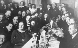 """<p>Family and friends are gathered for a Jewish wedding celebration in Kovno.Among those pictured are Jona and Gita Wisgardisky (standing at the back on the right).</p> <p>In the summer of 1941 soon after the German occupation of <a href=""""/narrative/5762"""">Lithuania</a>, the Wisgardisky family was forced into the Kovno <a href=""""/narrative/286"""">ghetto</a>. During a roundup of children in the ghetto in 1942, Henia (Gita and Jona's daughter) was hidden in a secret room that her father built in a pantry in their apartment. Later she was smuggled out of the ghetto and placed with the Stankiewicz family. Jonas Stankiewicz had worked as the foreman in Jona Wisgardisky's chemical plant before the war, and had taken it over after the occupation.</p> <p>After successfully securing a hiding place for their daughter, the Wisgardiskys fled from the ghetto. They found refuge on a potato farm, where they lived in a root cellar.</p> <p>Photograph taken in<a href=""""/narrative/3182"""">Kovno</a>, Lithuania, ca. 1938.</p>"""