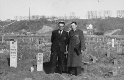 "<p>Secretary of the Kovno ghetto Jewish council <a href=""/narrative/11705/en"">Avraham Tory</a> stands with Zvi Brik (left), workshop administrator, in the cemetery of the <a href=""/narrative/3182/en"">Kovno</a> ghetto. Kovno, Lithuania, 1943.</p>"