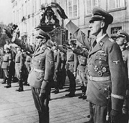 Reinhard Heydrich (right) and his deputy, Karl Hermann Frank (center), stand at attention during Heydrich's inauguration as governor ... [LCID: 64053]