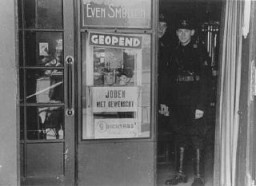 "<p>Members of the paramilitary organization of the Dutch Nazi Party stand in the doorway of a restaurant. The sign states ""Jews are not desired."" <a href=""/narrative/5543/en"">Amsterdam</a>, the Netherlands, 1941–42.</p>"