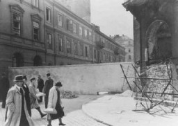 "<p>Polish civilians walk by a section of the wall that separated the <a href=""/narrative/2014/en"">Warsaw</a> ghetto from the rest of the city. Warsaw, Poland, 1940–41.</p>"