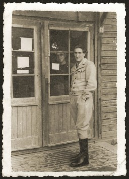 """<p><a href=""""/narrative/6365/en"""">Jewish DP</a> David Bromberg poses at the entrance to a barrack in the Ebensee displaced persons camp on October 30, 1946.</p>"""