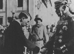 "<p>Recently appointed as German chancellor, <a href=""/narrative/43"">Adolf Hitler</a> greets President <a href=""/narrative/19342"">Paul von Hindenburg</a> in Potsdam, Germany, on March 21, 1933. This pose was designed to project an image of Hitler as non-threatening to the established order. This particular image is from a popular postcard. The photo also appeared widely in both the German and international press. Hitler appears in civilian dress, bowing in deference to the heavily decorated von Hindenburg. The March 5, 1933, elections had conferred legitimacy on Hitler's leadership.</p>"