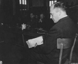 "<p>Friedrich Hoffman, holding a stack of death records, testifies about the murder of 324 Catholic priests who were exposed to malaria during <a href=""/narrative/3000/en"">Nazi medical experiments</a> at the <a href=""/narrative/4391/en"">Dachau</a> concentration camp. Dachau, Germany, November 22, 1945.</p>"