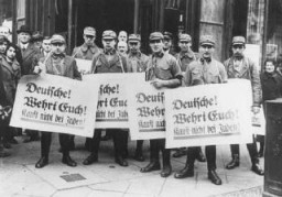 "<p>During the <a href=""/narrative/102/en"">anti-Jewish boycott</a>, SA men carry banners which read ""Germans! Defend Yourselves! Do Not Buy From Jews!"" Berlin, Germany, March or April 1933.</p>"