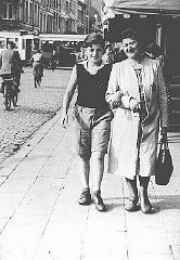 "<p>Shoshane Varmel Levy and her son, Jules, wearing the <a href=""/narrative/11750/en"">compulsory yellow badge</a>, on a street in Antwerp. Belgium, June 1942.</p>"