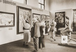 "<p>Visitors view the <a href=""/narrative/60322/en"">""Degenerate Art""</a> exhibition (<em>Entartete Kunst</em>) at the Munich Hofgarten in July 1937. Works by Lovis Corinth and Franz Marc are visible, among others.</p>"