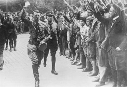 "<p class=""document-desc moreless"">Followed closely by an SS bodyguard, Adolf Hitler greets supporters at the fourth Nazi Party Congress in Nuremberg. Germany, August 1929.</p>