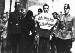 """<p>Umiliazione pubblica: """"Sono colpevole di inquinamento della razza"""". In questa fotografia si vede un uomo accusato di avere avuto una relazione illecita con una donna ebrea; il giovane viene costretto a camminare lungo le strade per essere umiliato pubblicamente. Affiancato da poliziotti tedeschi, egli è anche costretto a portare un cartello con la scritta """"Sono colpevole di inquinamento della razza"""".  Queste dimostrazioni miravano a punire i presunti colpevoli, facendone dei pubblici esempi e usandoli come deterrente per coloro che non condividevano le teorie razziali del Nazismo. Norden, Germania, luglio 1935.</p>"""