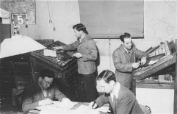 "<p>Jewish refugees work on a newspaper at <a href=""/narrative/35426/en"">Zeilsheim</a> displaced persons camp. Germany, between 1945 and 1948. The newspaper was titled <em>Unterwegs</em> (The Transient). </p>"