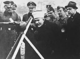Hadj Amin al-Husseini en compagnie de SS allemands et de membres bosniaques de la Waffen-SS au cours d'une visite officielle en Bosnie, vers