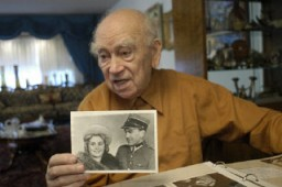 "<p><a href=""/narrative/10265/en"">Norman Salsitz</a> holds a photograph of himself and Amalie from 1945. 2004.</p>