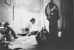 "<p><a href=""/narrative/11609/en"">Jan Karski</a> (standing), underground courier for the Polish government-in-exile. He informed the west in the fall of 1942 about Nazi atrocities against Jews taking place in Poland. Pictured in his office in Washington, DC, United States, 1944.</p>"