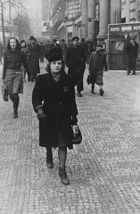 "<p>Elsa Eisner, marked with a Jewish badge, walks down a street in Prague. She, her mother, twin sister and other members of the family were deported to <a href=""/narrative/3673/en"">Auschwitz</a> in July 1942. Prague, Czechoslovakia, ca. 1941.</p>"