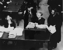 """<p>Chief Prosecutor Benjamin Ferencz presents evidence during the Einsatzgruppen Trial, <a href=""""/narrative/9545/en"""">Case #9 of the Subsequent Nuremberg Proceedings</a>. Ferencz is flanked by German defense lawyers Dr. Friedrich Bergold (right, counsel for Ernst Biberstein) and Dr. Rudolf Aschenauer (left, counsel for Otto Ohlendorf), who are protesting the introduction of certain documents as evidence.</p>"""