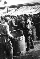 """<p><a href=""""/narrative/10135"""">Soviet prisoners of war</a> receiving their meager rations. More than three million Soviet prisoners of war died in German custody, mostly from malnutrition and exposure. Rovno, Poland, 1941.</p> <p><span style=""""font-weight: 400;"""">Second only to the Jews, Soviet prisoners of war were the largest group of victims of </span><a href=""""https://encyclopedia.ushmm.org/narrative/10962/en""""><span style=""""font-weight: 400;"""">Nazi racial policy</span></a><span style=""""font-weight: 400;"""">.</span></p>"""