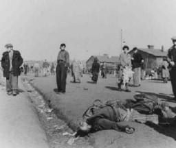 "<p>Soon after <a href=""/narrative/7842"">liberation</a>, camp survivors walk amidst dead bodies. Bergen-Belsen, Germany, after April 15, 1945.</p>"