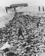 <p>Dr. Fritz Klein stands among corpses in a mass grave at Bergen-Belsen, after the liberation of the camp. He was required to assist in the burial of inmates who died there. Klein was a camp doctor at both Auschwitz and Bergen-Belsen. Germany, after April 15, 1945.</p>