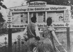 <p>A German couple reads an outdoor display of the antisemitic newspaper <em>Der Stürmer</em> (The Attacker). Germany, 1935.</p>