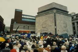 <p>A large crowd fills Eisenhower Plaza during the dedication ceremony of the United States Holocaust Memorial Museum. Flags of the liberating divisions form the backdrop to the opening ceremony. Washington, DC, April 22, 1993.</p>