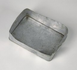"<p>Aluminum food container lid used by a Hungarian Jewish family on the <a href=""/narrative/11729"">Kasztner</a> train. The family had used the container on outings outside <a href=""/narrative/4669"">Budapest</a>. It later accompanied them to Bergen-Belsen, Switzerland and, finally, to the United States.</p>"