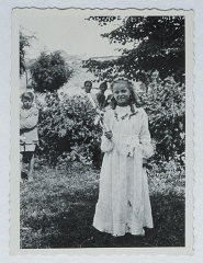 <p>Selma Schwarzwald poses outside while wearing her first communion dress. Selma lived in hiding as a Polish Catholic during the war. Busko-Zdroj, Poland, 1945.</p>