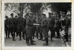 """<p>September 1, 1944, Richard Baer ceremonially accepts a copy of the construction plans from the Chief of the Central Construction Directorate of the Waffen SS, SS-Sturmbannführer Karl Bischoff, celebrating the opening of an SS military hospital (SS-Lazarette). Baer was the last commandant of the Auschwitz camp.</p> <p><span style=""""font-weight: 400;"""">From <a href=""""/narrative/10865/en"""">Karl Höcker's photograph album</a>, which includes both documentation of official visits and ceremonies at <a href=""""/narrative/3673/en"""">Auschwitz</a> as well as more personal photographs depicting the many social activities that he and other members of the Auschwitz camp staff enjoyed. These rare images show Nazis singing, hunting, and even trimming a Christmas tree. They provide a chilling contrast to the photographs of thousands of Hungarian Jews deported to Auschwitz at the same time. </span></p>"""