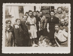 """<p>Jewish <a href=""""/narrative/6365/en"""">DPs</a> from the New Palestine displaced persons camp in <a href=""""/narrative/53446/en"""">Salzburg</a>, Austria, gather around a memorial dedicated to the Jewish victims of the Nazis. Among those pictured is Moniek Rozen (third from the left), Kazik Szancer (fourth from the left) and Rela Szancer (fifth from the left).</p>"""