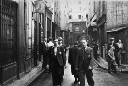 "<p>Jewish men wearing the mandatory <a href=""/narrative/11750/en"">Jewish badge</a> in the Jewish quarter of Paris. France, after June 1942.</p>"